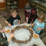 "This was a favorite ""messy"" activity for the Budding Birders. They smeared peanut butter on the wreath and then sprinkled it seed."