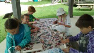 Kids making leaf prints in clay