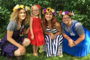 Photo of young girl and ladies dressed in flower crowns