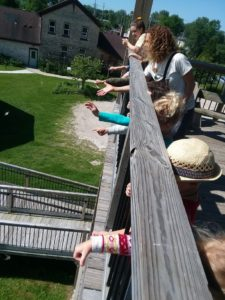 photo of kids dropping milkweed seeds from the observation tower