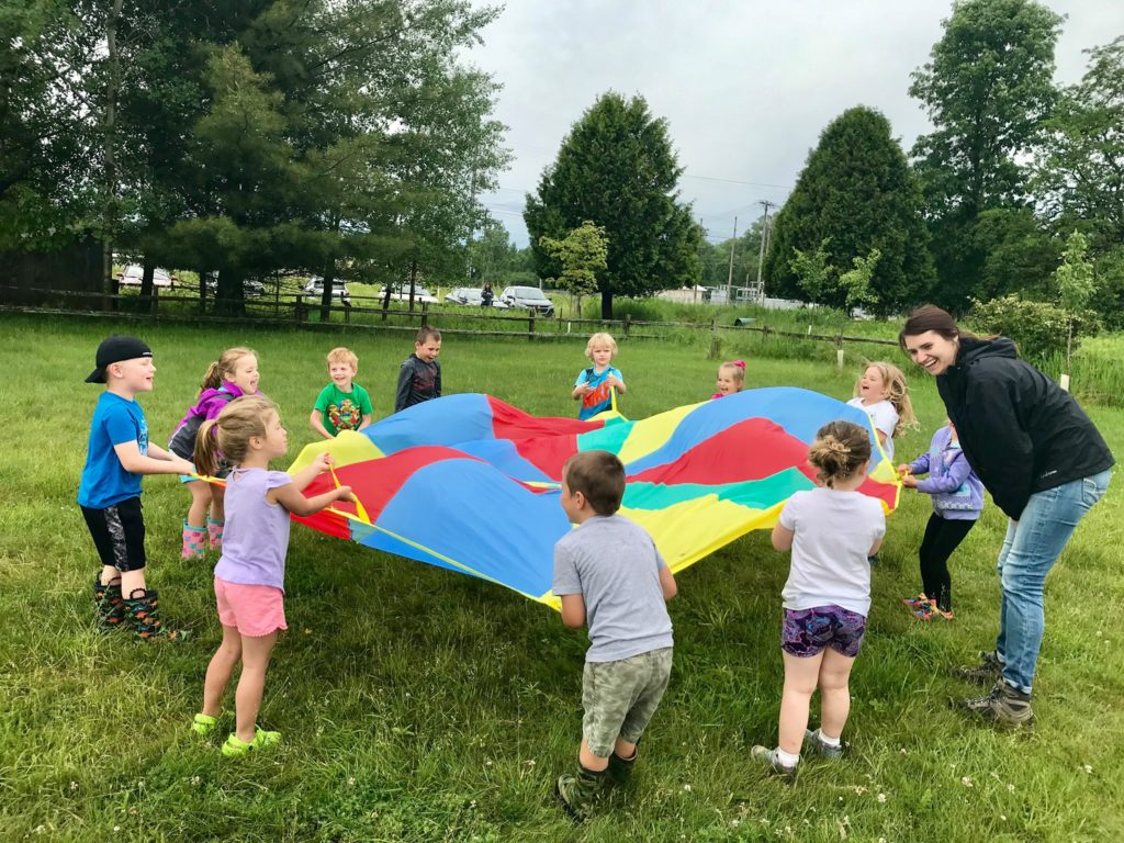 Little Wings campers playing with a large parachute