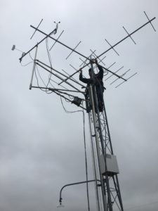 photo of man putting up motus antenna